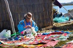 ILHAS DE FLUTUAÇÃO DE UROS, PUNO, PERU 31 DE MAIO DE 2013: Mulher nativa não identificada que veste os panos tradicionais, venden Foto de Stock Royalty Free
