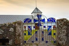 Ilhas Faroé, cruz celta do vitral azul em uma porta em Kirkjobur Imagens de Stock Royalty Free