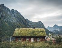 Ilhas Noruega de Lofoten - em setembro de 2018: Casa com o telhado e as montanhas tradicionais da grama no fundo em um nebuloso imagens de stock
