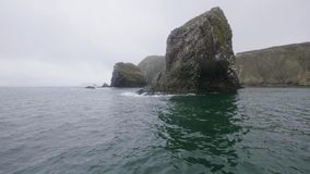 Ilhas rochosas bonitas com as montanhas e os pássaros que voam no céu nebuloso sobre a paisagem da água do mar video estoque