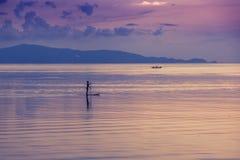 Ilhouette девушки на прибое МАЛЕНЬКОГО ГЛОТКА в море на заходе солнца Спорт, Стоковое Изображение