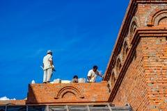 Ilinskoe, Russia - agosto 2018: I lavoratori migranti costruiscono un edificio fotografia stock libera da diritti