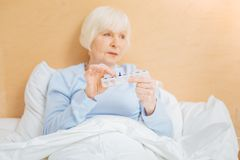 Ill aged woman sitting with her pillbox and looking into the distance. Convenient pillbox. Tired ill senior woman feeling unwell and holding a convenient pillbox Royalty Free Stock Photo