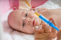 Ill baby is starring on syringe with immunization vaccine.  royalty free stock photos