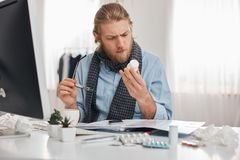 Ill bearded male office worker in blue shirt and scarf with spectacles concentrated on reading prescription of pills. Young manager with flu, sits at workplace Stock Photo