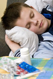 Ill in bed. An ill teenager boy in bed, sleeeping. Medicines (pills) in the foreground royalty free stock photos