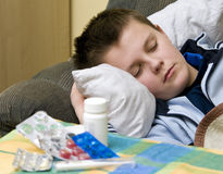 Ill in bed. An ill teenager boy in bed, sleeeping. Medicines (pills) in the foreground Royalty Free Stock Photography