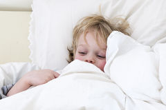 Ill boy. Sick boy, cuddled up under the duvet in his bed Stock Photos