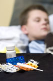 Ill boy. An ill teenager boy in bed. Focus on the medicines on the table royalty free stock photography