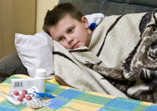Ill boy. An ill teenager boy in bed covered with a blanket. Medicines on the table stock image