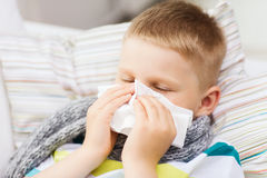 Ill boy with flu at home. Childhood, healthcare and medicine concept - ill boy with flu blowing nose at home Royalty Free Stock Image