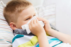 Ill boy with flu at home. Childhood, healthcare and medicine concept - ill boy with flu blowing nose at home Stock Photos