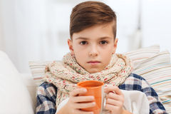 Ill boy with flu in scarf drinking tea at home. Childhood, healthcare, people and medicine concept - ill boy with flu lying in bed and drinking tea at home royalty free stock photography