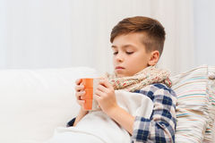 Ill boy with flu in scarf drinking tea at home. Childhood, healthcare, people and medicine concept - ill boy with flu lying in bed and drinking tea at home Stock Photography