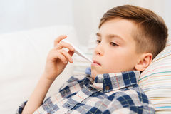Ill boy with flu and thermometer at home Stock Photography