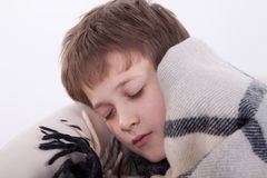 The ill boy Has fallen asleep in an armchair. The ill boy, he is covered by a checkered plaid Stock Image