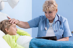 Ill boy having high fever. And his doctor Royalty Free Stock Photo