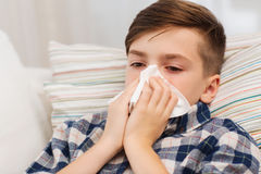Ill boy lying in bed and blowing his nose at home Royalty Free Stock Images
