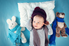 Ill boy lying in bed. Cute child with fever and hat on head stock image