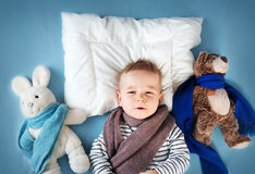Ill boy lying in bed Royalty Free Stock Photos