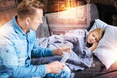 Ill boy sleeping while his father holding pills and water for him. Ill child. Tired little boy feeling unwell and sleeping while his kind loving worried father Stock Images