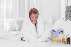 Ill boy suffering from cough. At home stock image