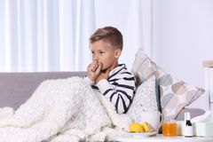 Ill boy suffering from cough on sofa. At home stock images