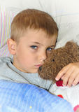 Ill boy with teddy bear. Little boy with teddy bear toy in the bed Royalty Free Stock Image