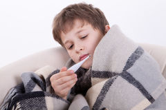 The ill boy with a thermometer. Measures temperature Royalty Free Stock Image