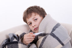 The ill boy with a thermometer. Measures temperature Royalty Free Stock Photography