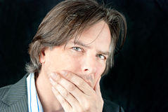 Ill Businessman Covers Mouth. Close-up of a ill businessman covering his mouth Stock Image