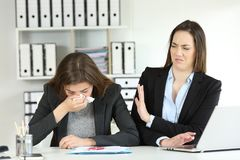 Ill businesswoman and a colleague rejecting her. Ill businesswoman blowing and a colleague rejecting her at office Royalty Free Stock Photos