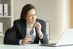 Ill businesswoman complaining and taking pill at office. Ill businesswoman complaining and taking pill working sitting in a desktop at office Stock Image