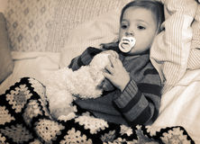 Ill child. Child baby or toddler ill or sick laying on sofa with teddy and dummy in mouth in bleached sepia monochrome Stock Photos