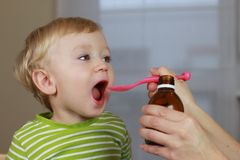 Ill child with cough syrup Royalty Free Stock Images