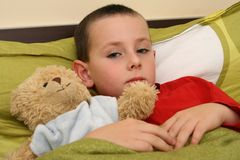 Ill child with flu. Child and sweet teddy bear lying in bed with flu and fever. Child with a temperature Royalty Free Stock Images