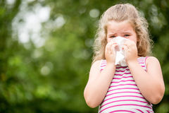 Ill child with flu sneezes. Ill child with a cold or flu sneezes and cleans nose with tissue Stock Photo