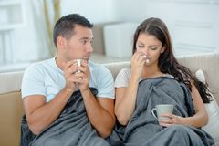 Ill couple sitting in bed drinking tea. Sik Royalty Free Stock Photo