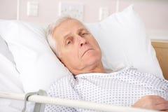 Ill dell'uomo maggiore nel letto di ospedale Fotografia Stock