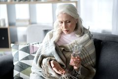 Sick mature lady curing herself by medication. Ill desperate senior woman is taking a pill while sitting on sofa at home. She is holding glass of water Stock Photo