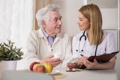 Ill elderly man with medicines. Photo of doctor and ill elderly men with medicines Stock Images