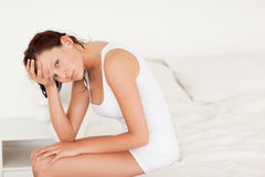 Ill-feeling woman sitting on her bed Royalty Free Stock Photography