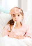 Ill girl child with thermometer and caring mother Stock Photography