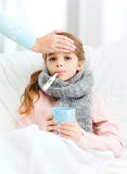 Ill girl child with thermometer and caring mother. Healthcare and medicine concept - ill girl child with thermometer in mouth, cup of hot tea and caring mother royalty free stock photography