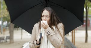 Ill girl coughing walking under the rain stock footage