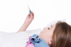 Ill girl looks at the thermometer. Royalty Free Stock Images