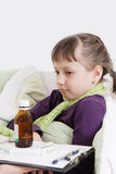 Ill girl lying in bed in front different medicine Royalty Free Stock Image