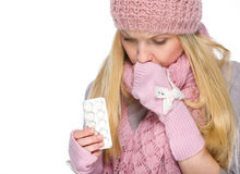 Ill girl in winter clothes holding pills pack. Isolated on white Royalty Free Stock Image