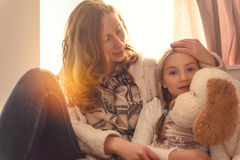 Ill giving solace. Mother giving daughter solace while illness royalty free stock photo