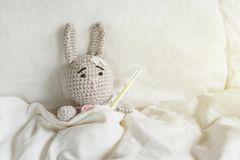 Ill Grey toy rabbit with thermometer and plaster on head in white bedroom. Stock Photo